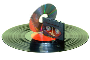 A compact disc and an audio cassette resting on a record