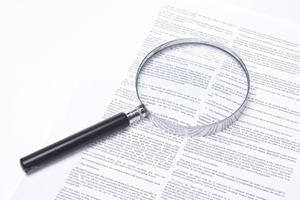A magnifying glass analysing a contract
