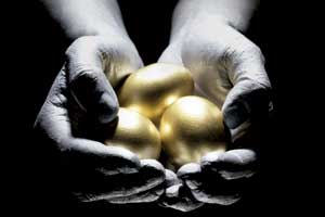 A pair of cupped hands holding golden eggs