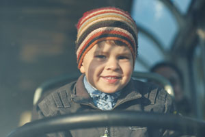 A child at the steering wheel of a bus