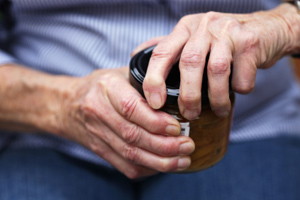An elderly person with arthritic hands trying to open a jar