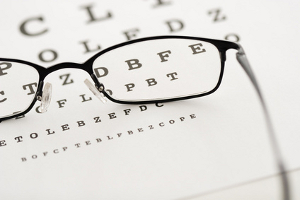 A pair of glasses placed on an eye chart