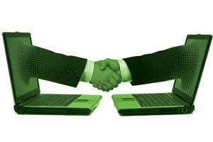 Two laptops facing each other with an arm protruding from each and shaking hands