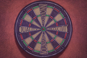A dartboard with 'quality', 'innovation', 'productivity' and 'prevention' forming target areas