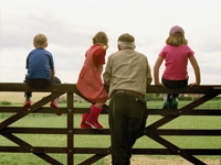 Family looking at a field while resting on a fence