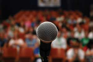 A single microphone with a blurred audience in the background