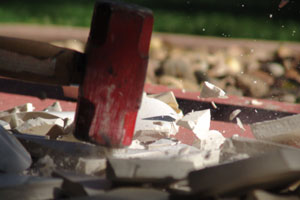 A porcelain ornament being smashed with a hammer
