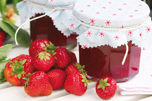 A jam jar next to several strawberries