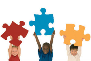 Three children, each holding a large jigsaw piece