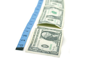 A tape measure measuring the length of a line of dollars