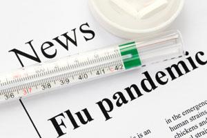 Newspaper headline saying 'flu pandemic' beside a syringe