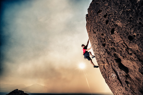 Man climbing rocky cliff