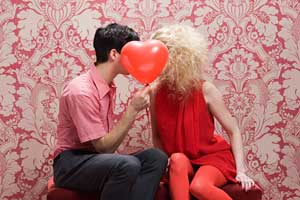 A young man an woman facing each other, their faces obscured by a heart-shaped balloon