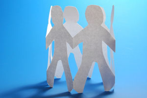 Paper cut outs of a team of people against a blue background