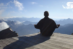 A man meditating on a mountain top