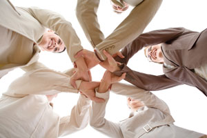 Upwards shot of people in a circle holding hands