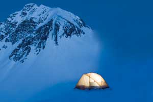 A tent against the backdrop of a mountain in the snow