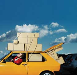 A car overloaded with boxes on its roof