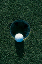 A golf ball going into a hole