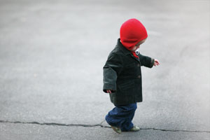 Little boy walking along a crack in pavement with red hat on