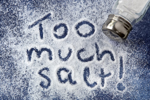 'Too much salt' written into a pile of salt spread out on a counter