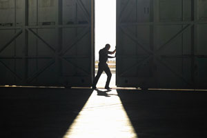 A man pushing open the door of a large warehouse