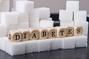 Diabetes spelled with lettered cubes sitting on sugar cubes